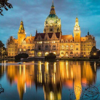 Bild von einem Schloss in Hannover bei Abenddämmerung, welches sich im Wasser spiegelt