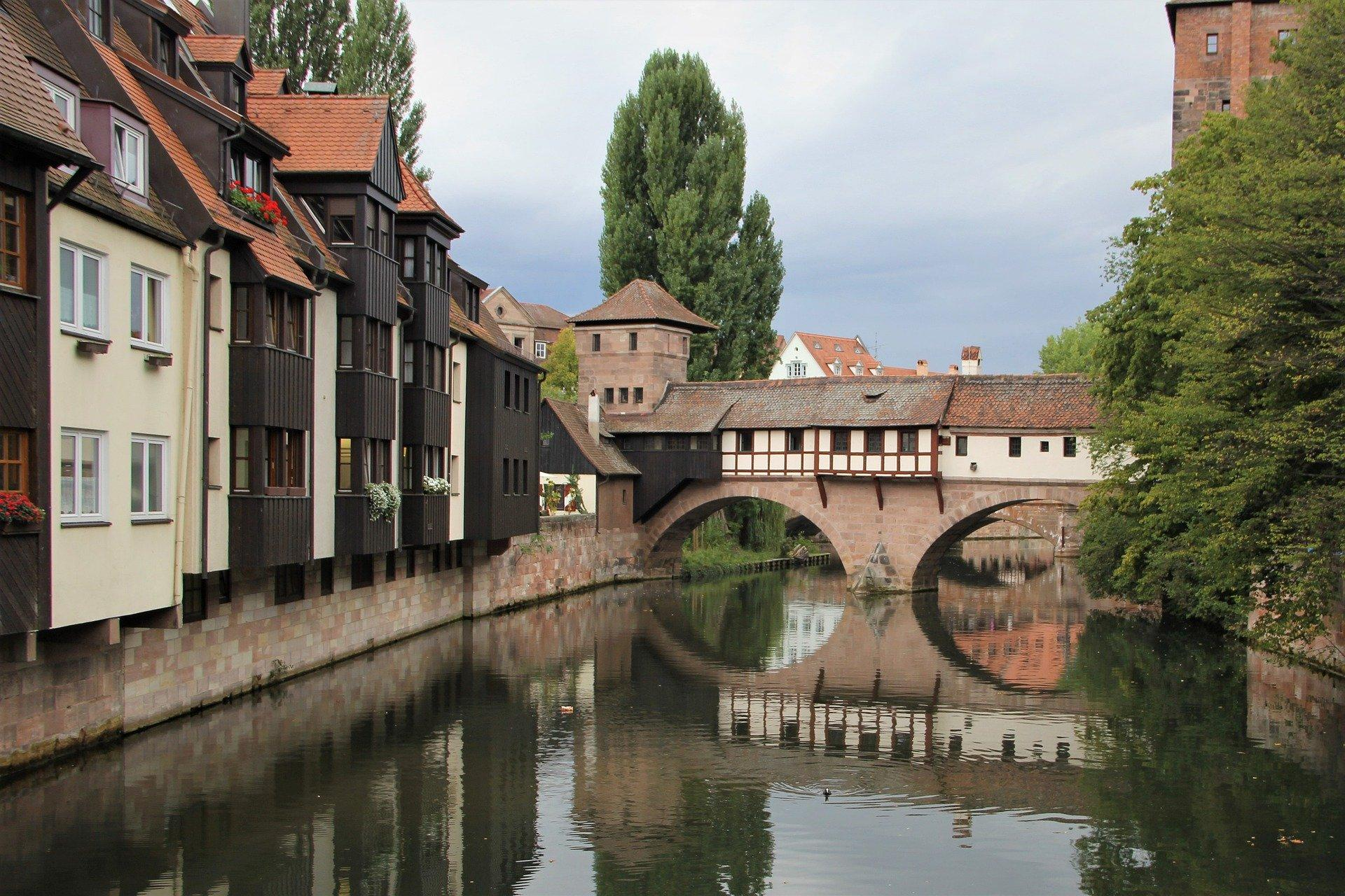 Bild von einer historischen Nürnberger Brücke, die sich im Wasser spiegelt