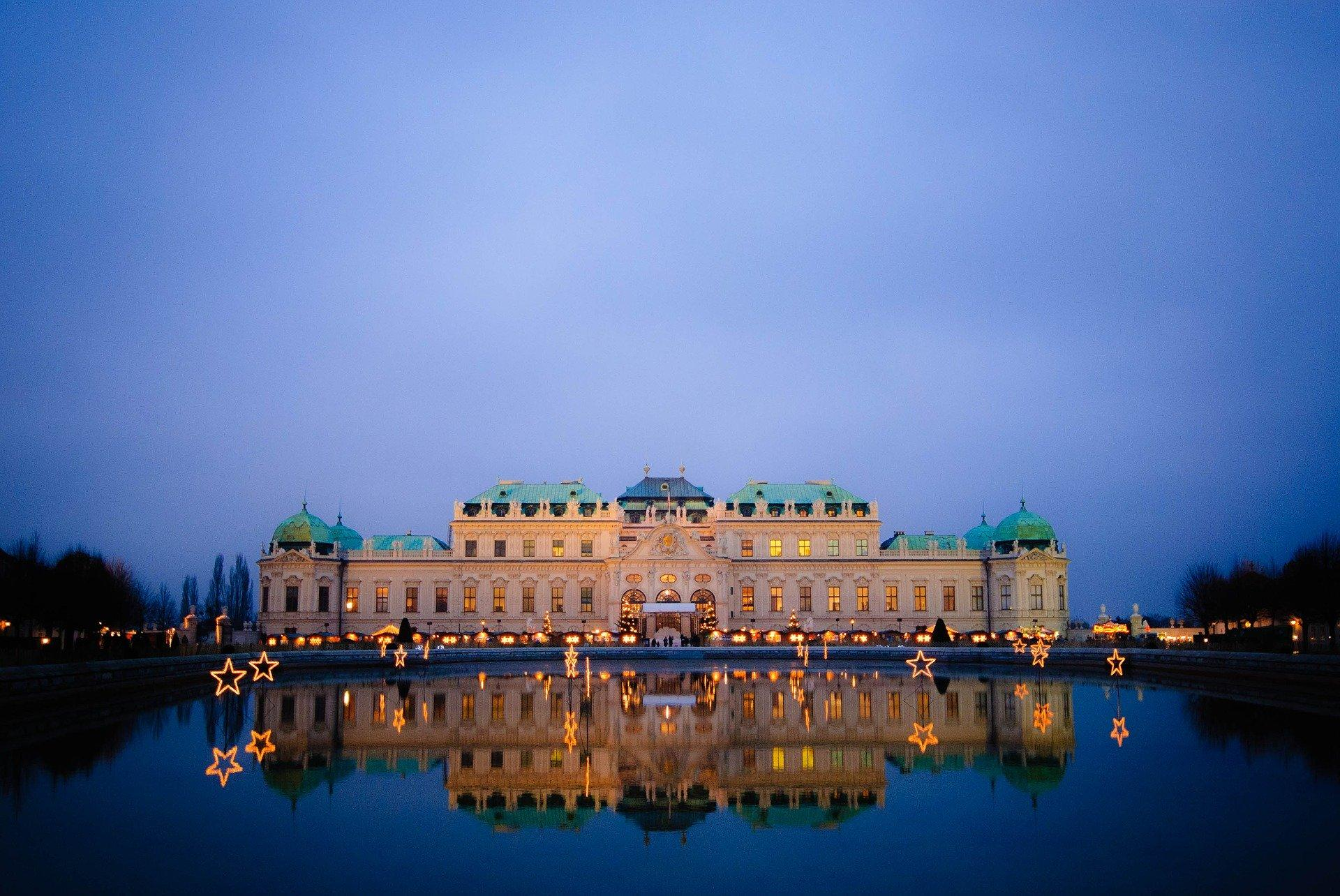 Bild von schönem Schloss in Wien welches sich im Wasser bei Abenddämmerung spiegelt