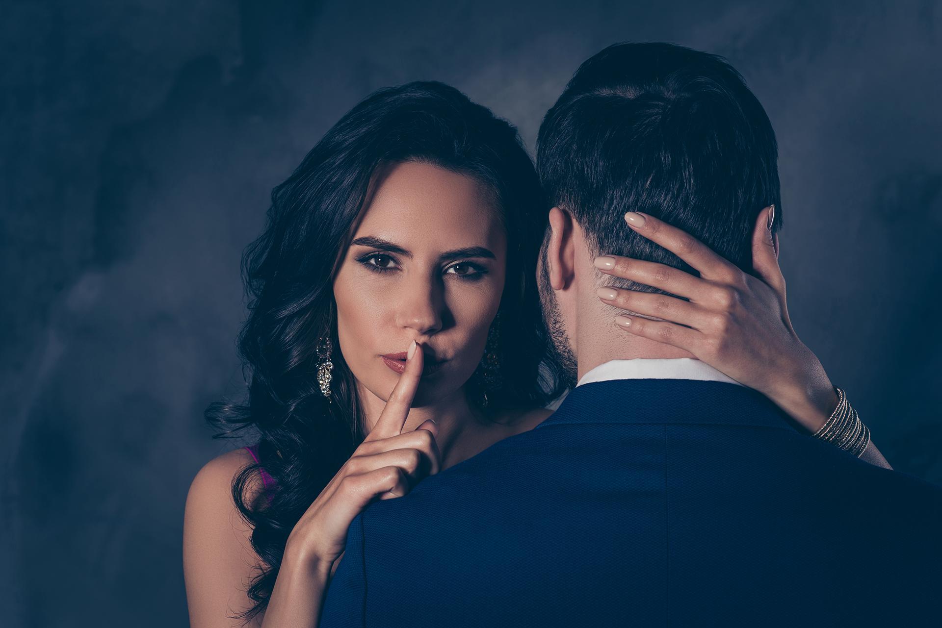 Bild von einer Dame, die einen Callboy gebucht hat und mit dem Zeigefinger auf dem Mund signalisiert, dass dieses Callboy Abenteuer ein Geheimnis bleiben wird.