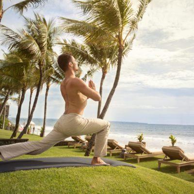Ein Callboy als Personal Trainer macht Übungen auf dem Rasen direkt am Strand