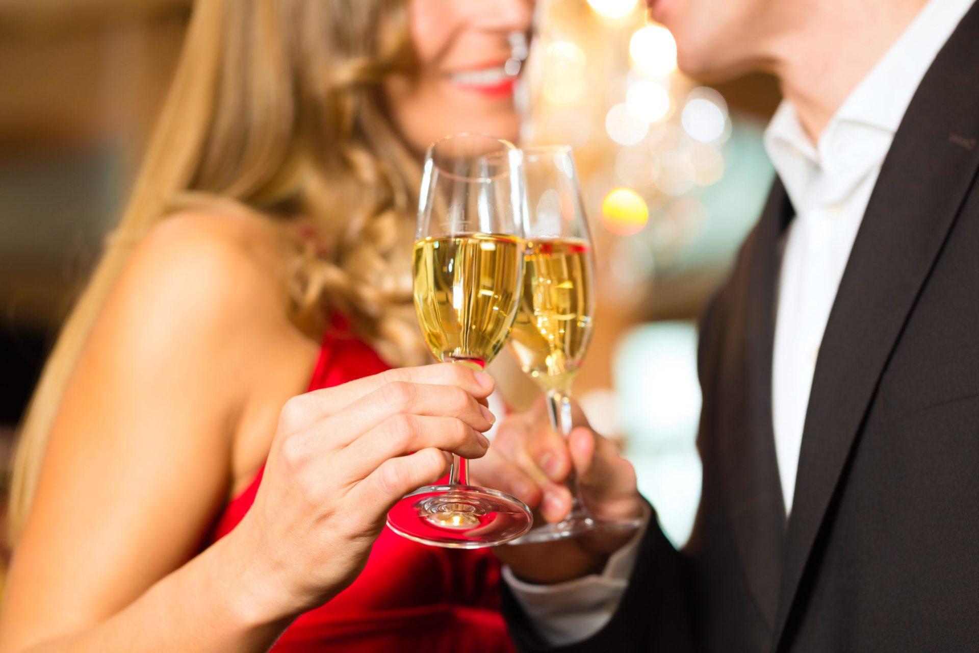 Eine blonde Dame stößt mit einem Callboy bei einem Sektglas an. Beide sind festlich gekleidet