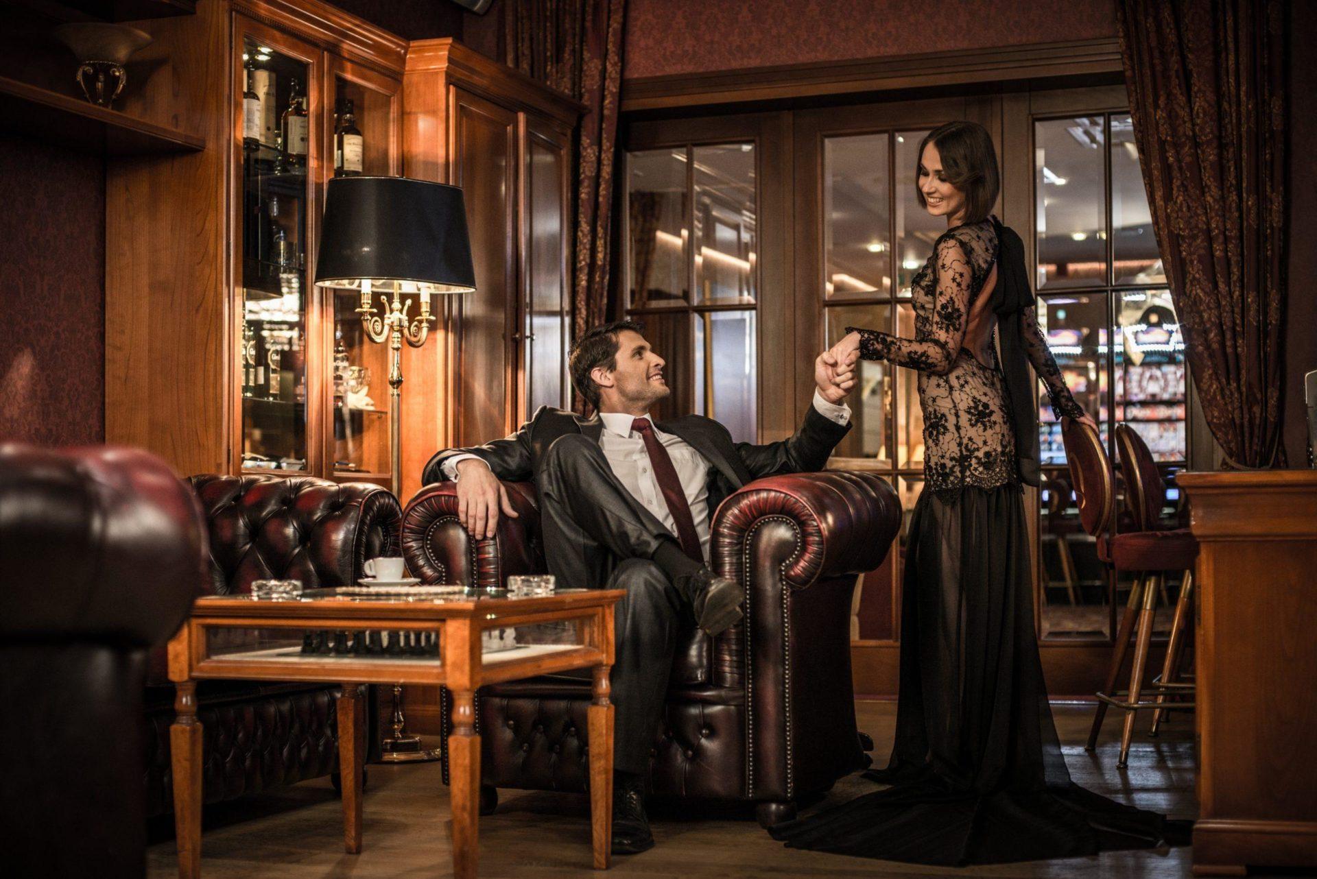 Eine lasziv gekleidete Dame hält einem in einem Sessel sitzenden Mann die Hand.