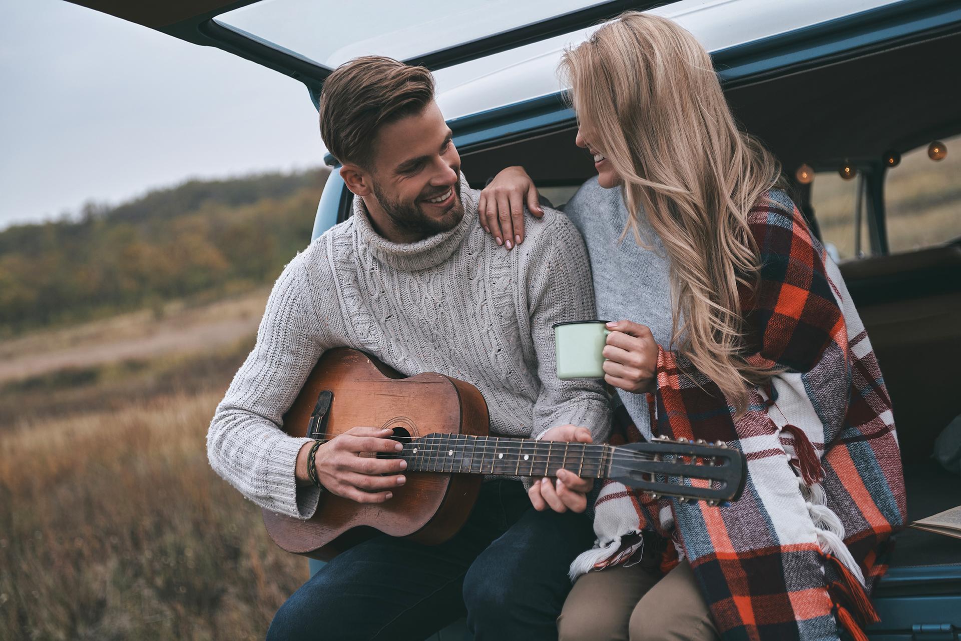 Ein Callboy spielt als Begleiter für Freitzeitaktivitäten ein Lied auf der Gitarre für eine neben sitzende hübsche blonde Dame