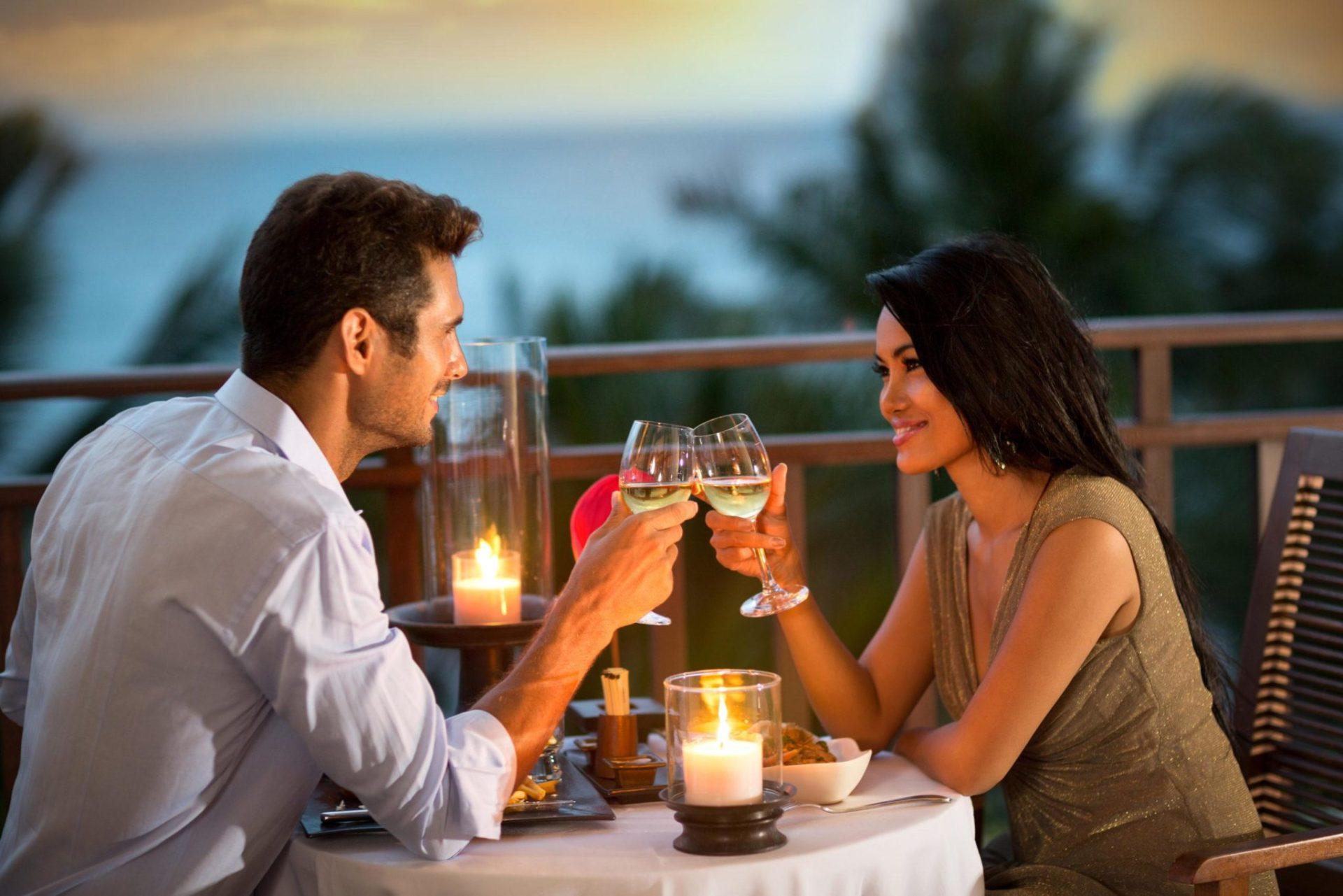 Eine Dame stößt beim Abendessen mit Ihrem Callboy bei einem Glas Weißwein an