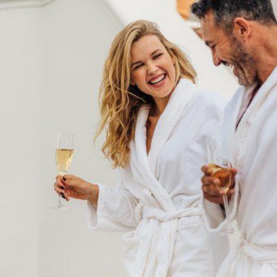 Ein Callboy begleitet eine Dame in eine Therme oder Sauna. Beide tragen Bademäntel und halten ein Sektglas in der Hand.