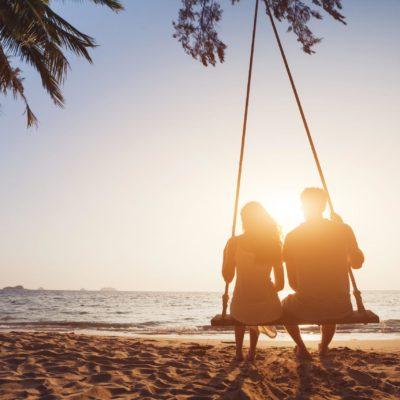Eine Dame sitzt neben einem Callboy auf einer Schaukel direkt am Strand und schaut den Sonnenuntergang
