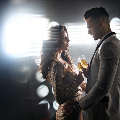Ein fein angezogener Gigolo hält eine Dame am Oberschenkel und sie stoßen mit einem Glas Champagner an