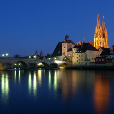 View over danube to Regensburg with stone bridge and cathedral at night