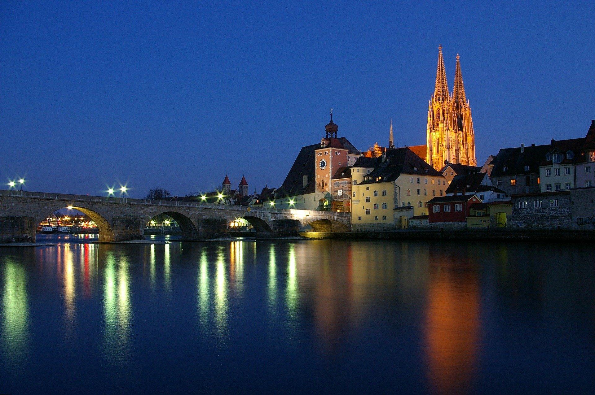 Blick über Donau auf Regensburg mit steinerner Brücke und Dom bei Nacht