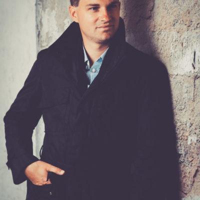 Callboy Alex aus Wien trägt einen Mantel