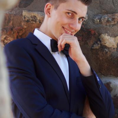 sympatisch grinsender junger Mann in dunklem Anzug