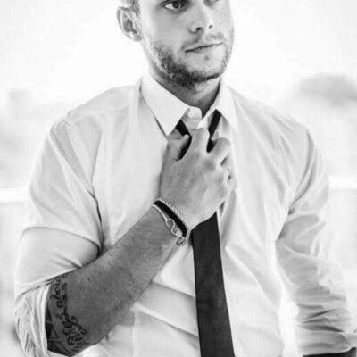 Hübscher Mann in weißem Hemd und schwarzer Krawatte