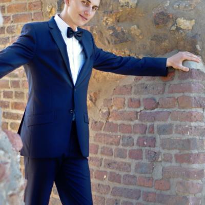 Netter Mann im Anzug, der sich an einer Mauer abstützt