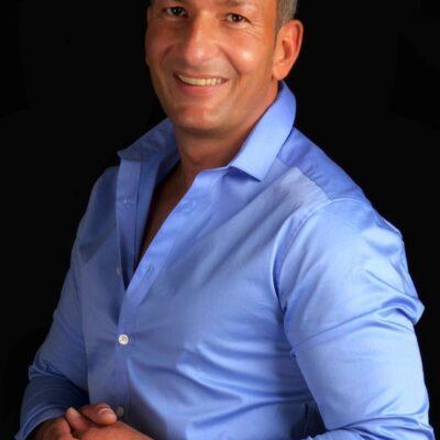 Lächelnder Mann in blauem Hemd mit grauen Haaren