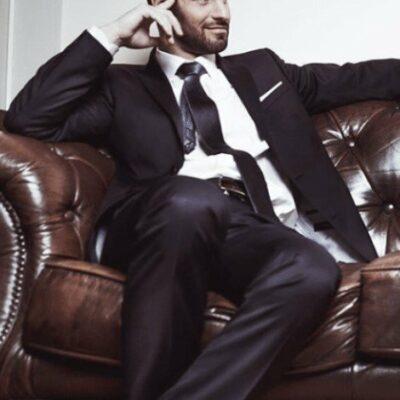 Freundliches Männermodell im Anzug sitzt auf einer braunen Ledercouch