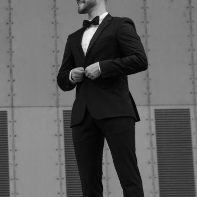 Attraktiver Mann in schwarzem Anzug mit Fliege