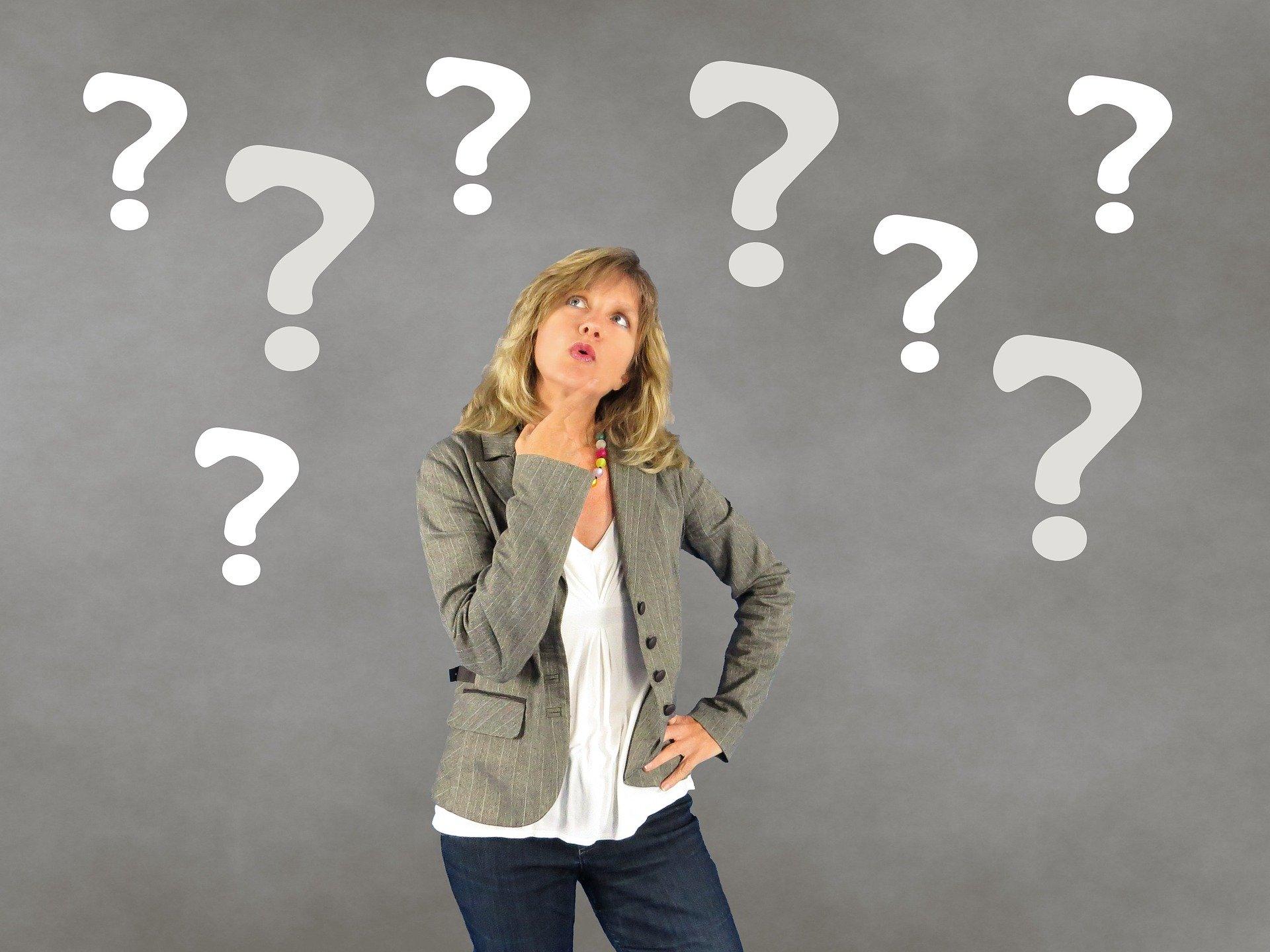 Callboy buchen – Frau betrachtet Fragezeichen vor grauem Hintergrund