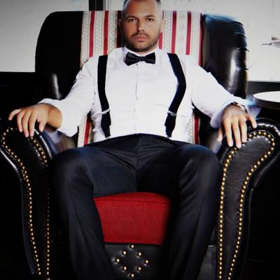 Wiener Callboy, der auf einem roten Sessel sitzt mit weißem Hemd und Hosenträgern