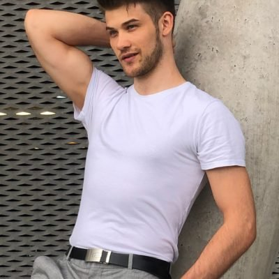 Gutaussehender Gigolo in weißem T-Shirt und Fashionblick