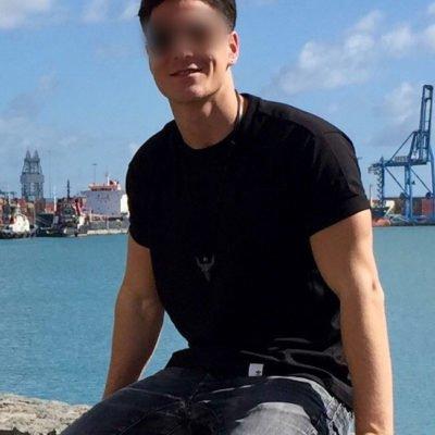 Hübscher junger Mann in dunklem Shirt mit Wasser im Hintergrund