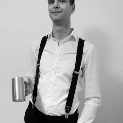 Mann mit Hosenträgern und einem Getränk in der Hand