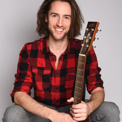 Freundliches Männermodell in rotem Hemd und mit Gitarre
