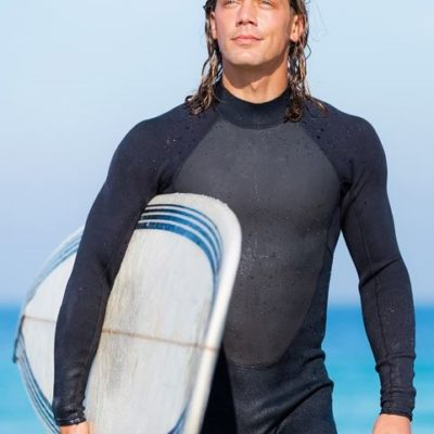 Attraktiver Surflehrer und männliches Modell am Strand mit Surfbrett unterm Arm