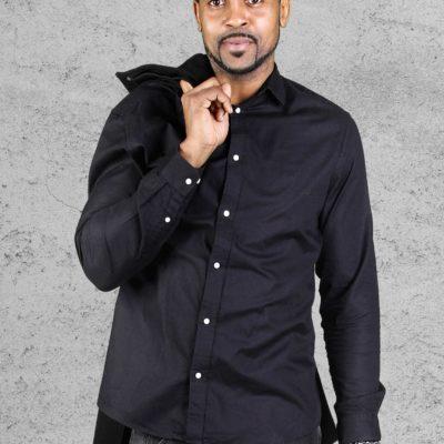 Hübsches Männermodel in dunklem Hemd und Sakko über der Schulter aus Osnabrück