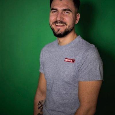 Hübscher Mann in grauem T-Shirt und freundlichem Grinsen