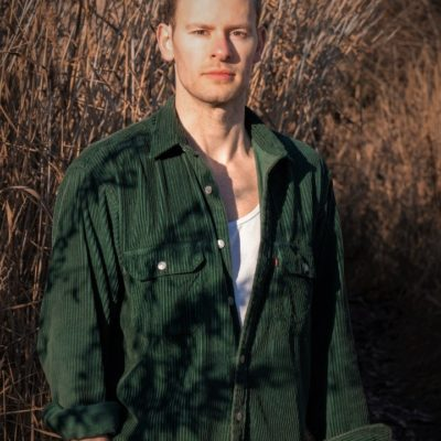 Attraktiver Herr aus Leipzig in grünem Hemd vor einem Kornfeld