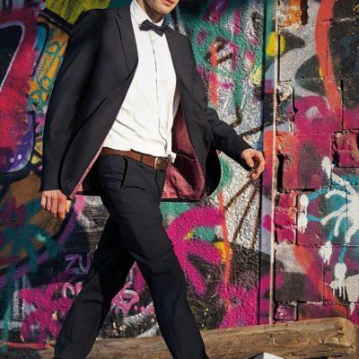 Gepflegter Mann im Anzug vor einer Wand mit Graffitis