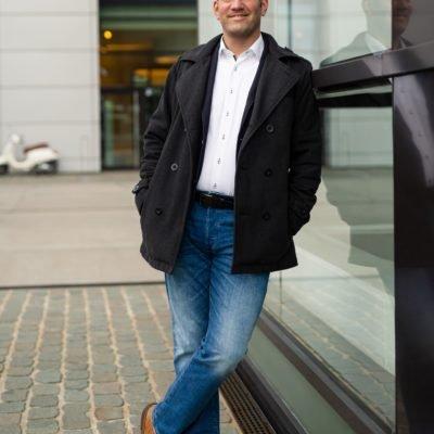 Sympathischer Herr in Jeanshose lehnt an Glasfassade