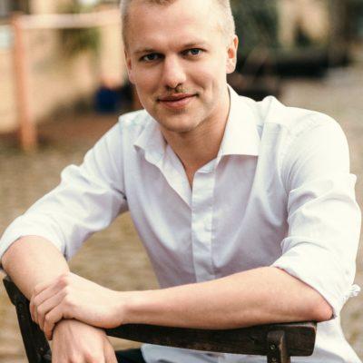 Hübsches Männermodell sitzt lässig auf einem umgedrehten Stuhl