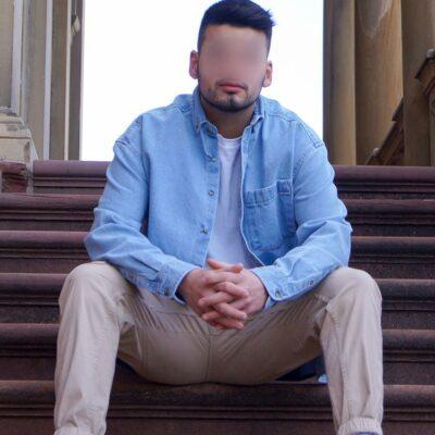 Männermodell aus Heidelberg auf einer Treppe sitzend