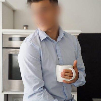 Lächelnder Herr mit einer Tasse in der Hand