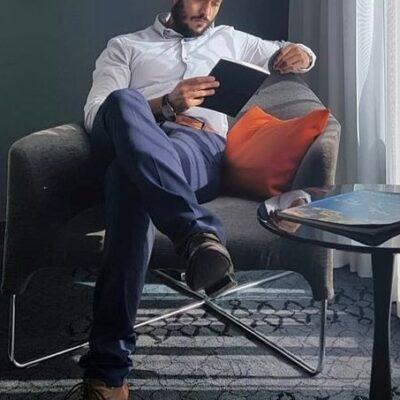 Freundlicher Herr, der in einem Sessel sitzt mit einem Buch in der Hand