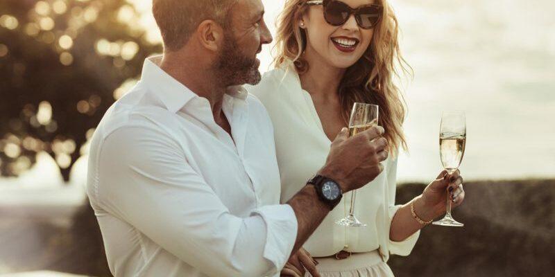 Eine Dame trinkt amüsiert Sekt mit einem Callboy